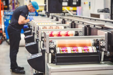 Operator at ProPrint Group checking the flexographic press for label printing.